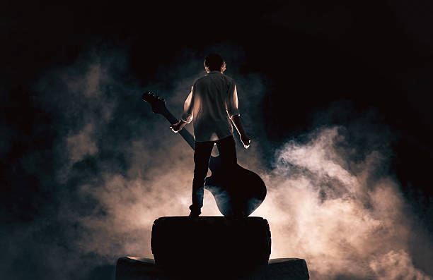 rock musician and large guitar, a lot of smoke - popular music concert stock photos and pictures