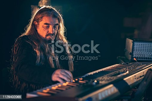 Rock musician playing keyboard on stage