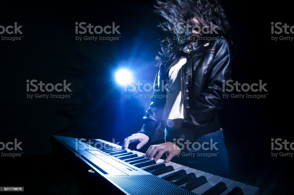 Rock musician playing keyboard on stage stock photo