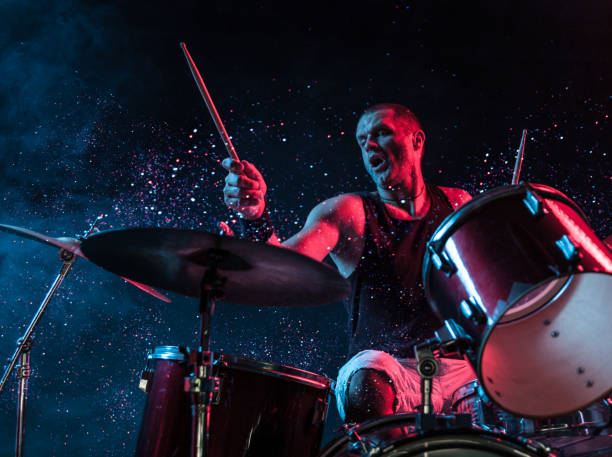 Rock N Roll Drummer Sparkles In The Air A man playing drums on stage with sparkles exploding off the drums. drummer stock pictures, royalty-free photos & images