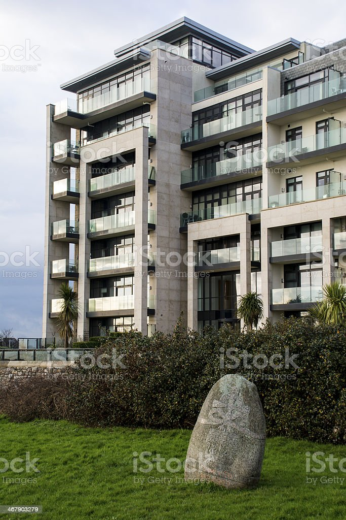 Rock next to azure apartments on Plymouth Hoe stock photo
