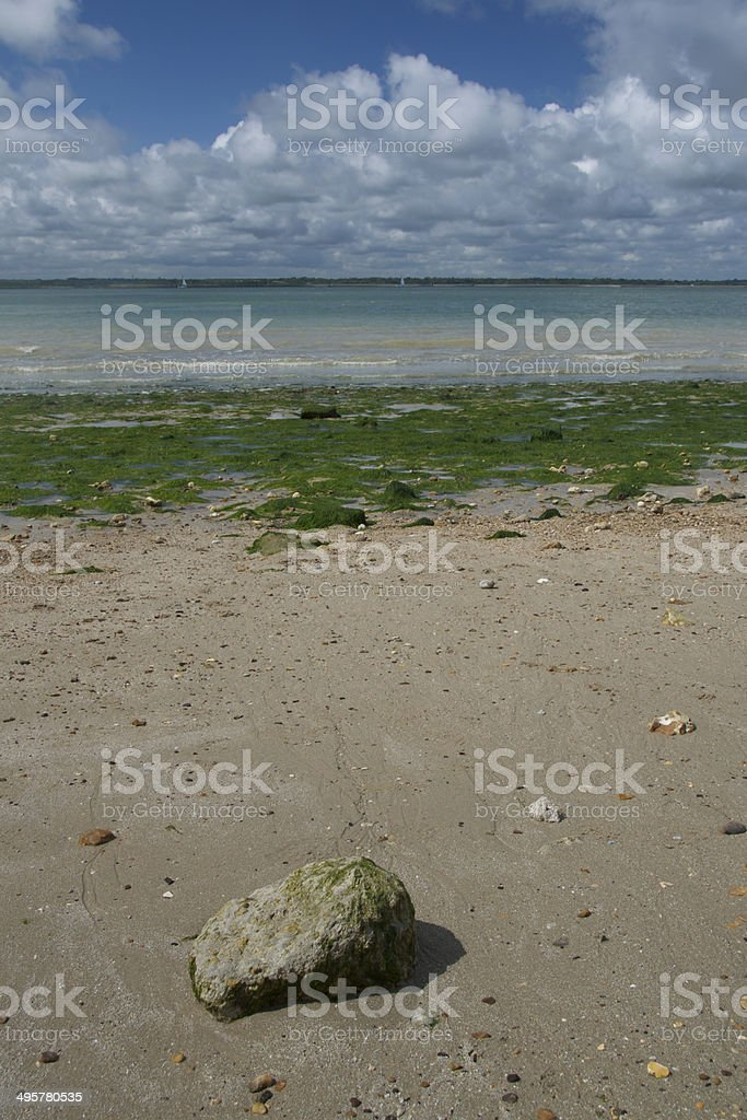 Rock on seaweedy beach overlooking Solent stock photo