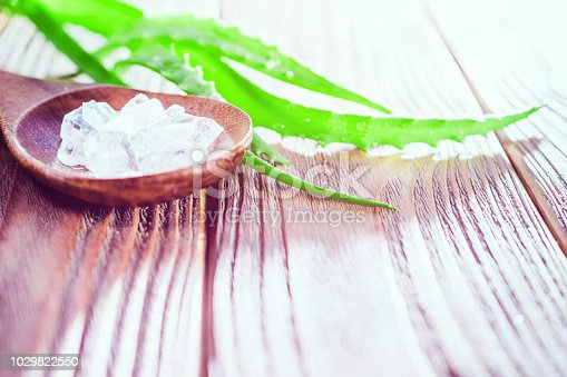 istock rock salt minerals and aloe vera gel on wooden background. organic skin care and natural cosmetic for sensitive skin. aloe vera leaf. alternative medicine, spa and skin care concept with copy space. 1029822550
