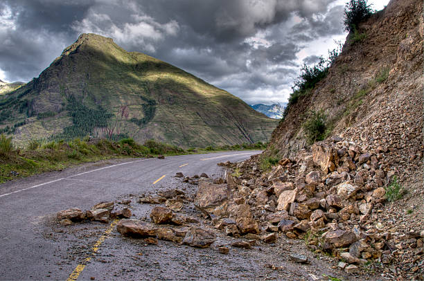 Rock slide with damage on the road during a storm Rock Slide - HDR Image - Multiple Exposures used to capture full dynamic range eroded stock pictures, royalty-free photos & images