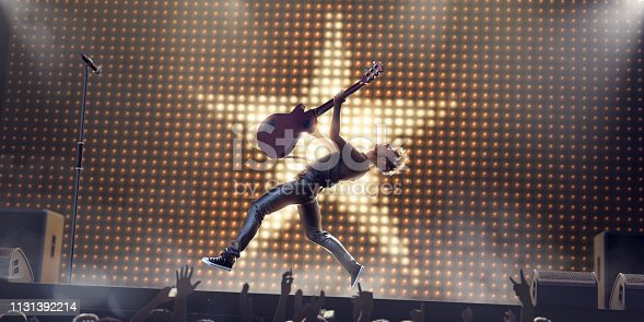 A young male rock star performing live on stage in front of a silhouetted crowd, jumpa in mid air, leaning backwards, holding electro-acoustic guitar above his head. The performer jumps in front of a wall of light bulbs in a star shape on stage with speakers, amplifiers and microphone.