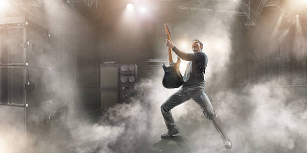 Rock Star Male rock star musician in dramatic pose wearing black clothes and leather trousers, holding up generic guitar and singing with mouth open and head back.  The guitarist is performing on a generic small indoor floodlit stage in music venue, full of sound equipment and speaker stack with haze and dry ice smoke effects.  guitarist stock pictures, royalty-free photos & images
