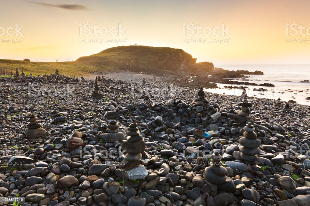 Rock Towers at Sunrise on a Pebbly Beach stock photo