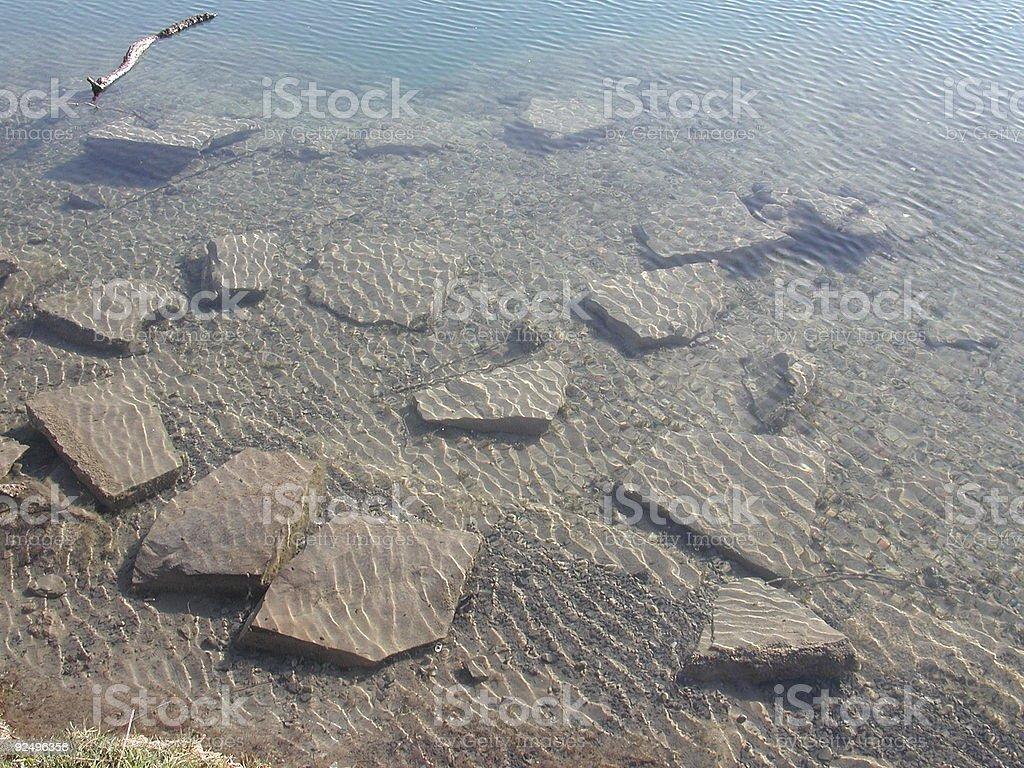 Rock under slightly rippled water royalty-free stock photo