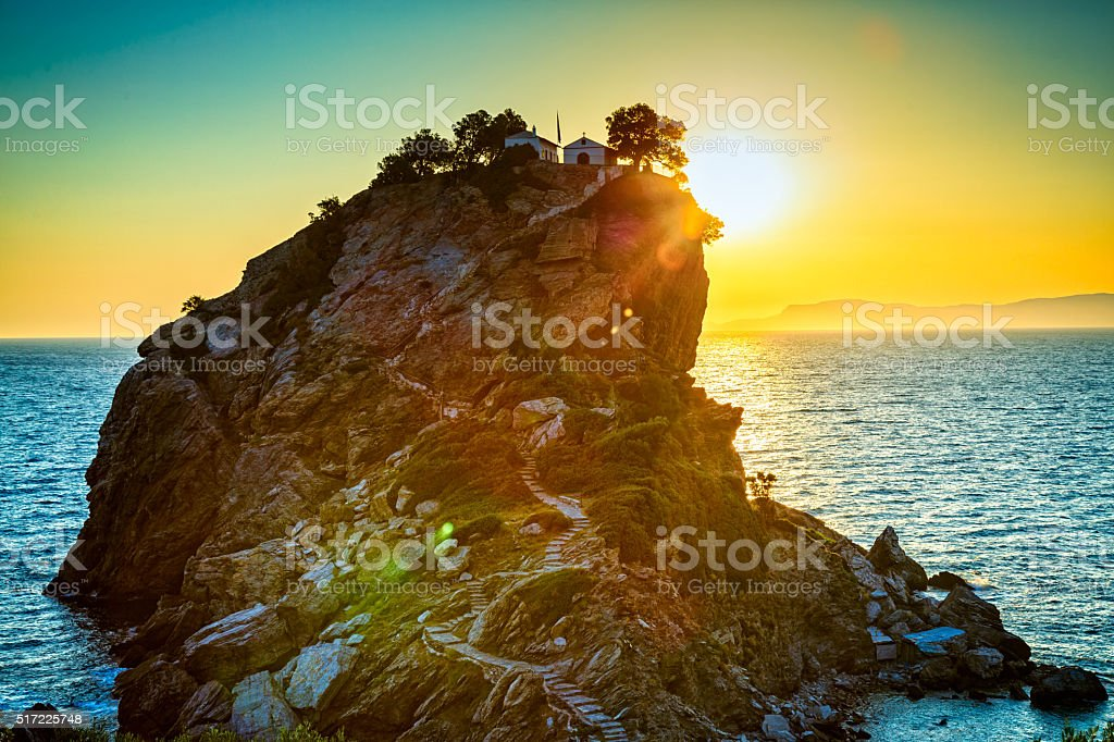 Rock with Agios Ioannis church on Skopelos island at sunrise stock photo