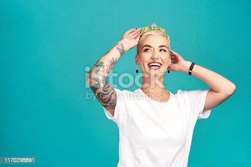 Studio shot of a young woman putting a crown her head against a turquoise background