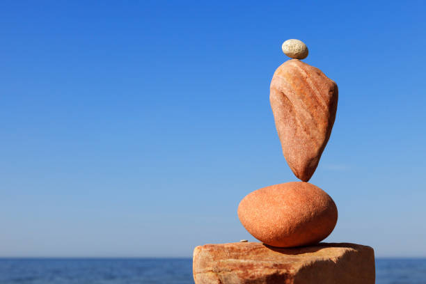 Rock zen pyramid of red pebbles on the beach. Concept of Life balance, harmony and meditation stock photo