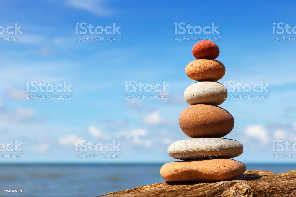 Zen Felspyramide des weißen und rosafarbenen Steinen auf einem Hintergrund von blauem Himmel und Meer. – Foto