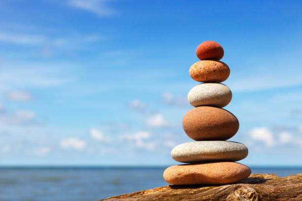 Rock zen pyramid of white and pink stones on a background of blue sky and sea. stock photo