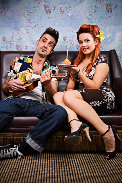 rockabilly paar ukulele und halten cupcake mit kerze - musik kuchen stock-fotos und bilder