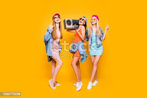 Rock-and-roll sneakers jeans eyewear peace symbol leisure rest relax concept. Portrait of funky trio having stereo audio player enjoying time together isolated on vivid yellow background