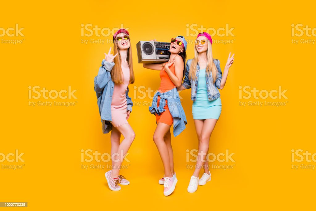 Roll baskets jeans lunettes paix symbole loisirs reste relax concept. Portrait de funky trio ayant lecteur audio stéréo profiter de temps ensemble isolé sur fond jaune vif - Photo