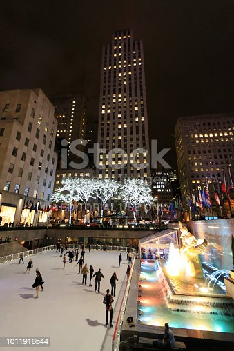 Manhattan, New York City, USA, November 1st, 2014. Night shot showing the Rockefeller Center Skating Rink, the in vibrant colors illuminated fountain and the surrounding skyscrapers. Few people skating on the ice.