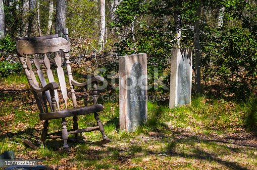 An old wooden rocking chair rests next to a pair of ancient headstones in a Cape Cod cemetery.
