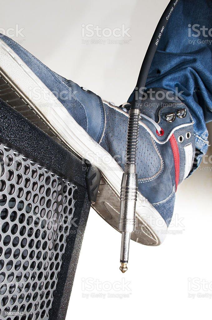 Rocker's foot on an amplifier. royalty-free stock photo