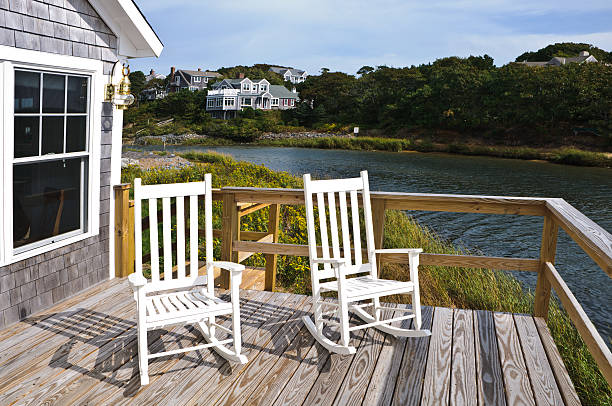 Rockers on the Deck Two white rockers on a deck of a small summer cottage on Cape Cod cape cod stock pictures, royalty-free photos & images