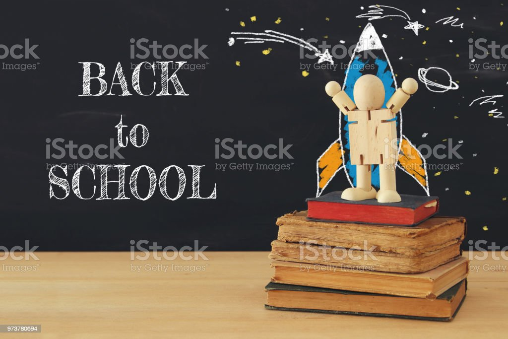 rocket and space sketches with wooden dummy in front of classroom blackboard. stock photo