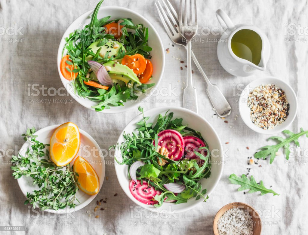 Rocket , beets, avocados, carrots, seeds, nuts detox salad with orange dressing on a light background, top view. Vegetarian healthy eating concept stock photo