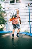 Little boy playing astronauts on trampoline