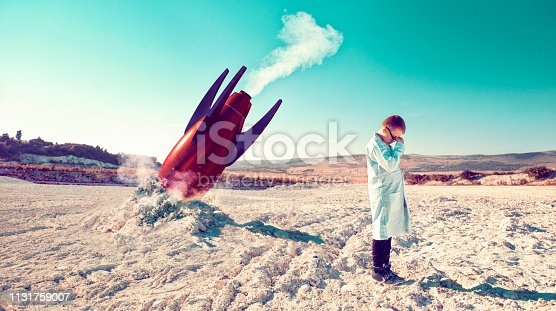 Child around 10 years old stands on a field after a failed rocket launch. He covers his head in his hands. He wears a lab coats like a real scientist.