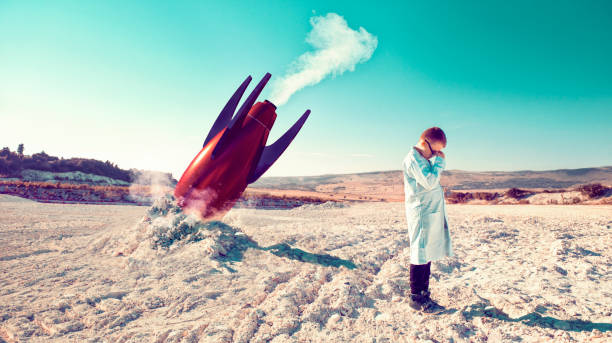 Rocket fails and falls to the ground while child in lab coat shows his disbelief Child around 10 years old stands on a field after a failed rocket launch. He covers his head in his hands. He wears a lab coats like a real scientist. failure stock pictures, royalty-free photos & images