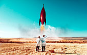 Two children around 8 and 10 years old stand on a field and lanch a red rocket. The rocket takes off and the children looks to the sky. They wear lab coats and it looks to be a very ambitious scientific experiment.