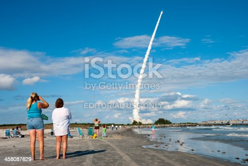 Cocoa Beach, Florida, USA - December 20, 2007: A rocket launches from Cape Canaveral as people watch from the beach at Jetty Park in Cocoa Beach, just to the south of the launch site. The rocket is a Delta II and carries a Global Positioning System satellite designed by Lockheed Martin.
