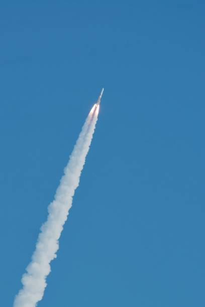 A rocket launches into the blue sky