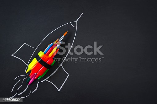Rocket ship made by crayons and felt tip pen on blackboard background