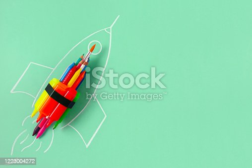 Rocket ship made by crayons and felt tip pen on green background with copy space
