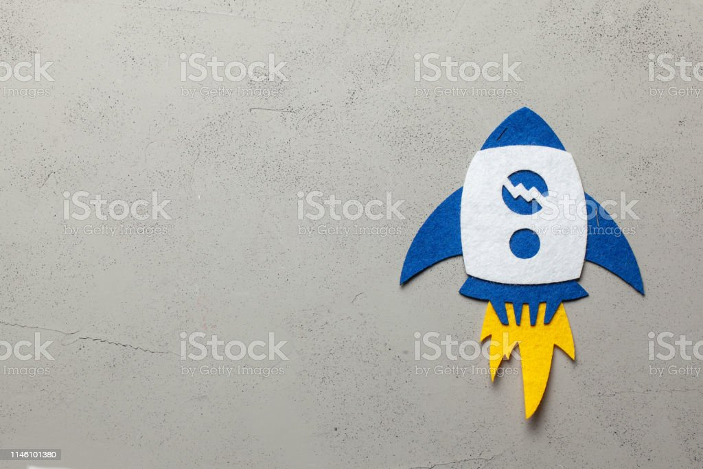 Rocket with fire on a gray background. Copy space for text