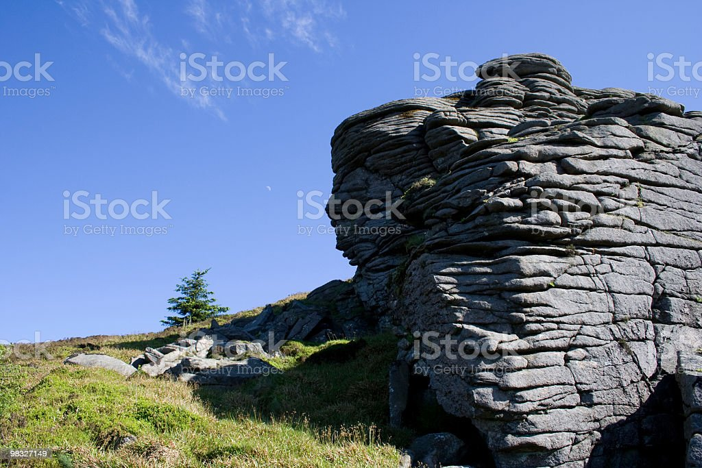 Rockface and lone pine tree on mountain top royalty-free stock photo