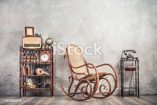 istock Rocking chair, old telephone, broadcast radio, retro camera, frame blank, globe, books, antique binoculars, alarm clock, carnival mask, golden key, souvenirs on shelf. Vintage style filtered photo 1152680316