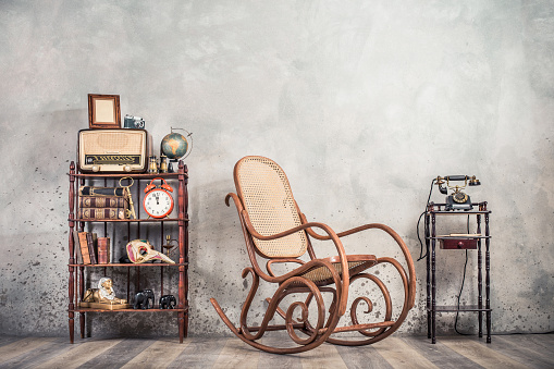 Rocking chair, old telephone, broadcast radio, retro camera, frame blank, globe, books, antique binoculars, alarm clock, carnival mask, golden key, souvenirs on shelf. Vintage style filtered photo