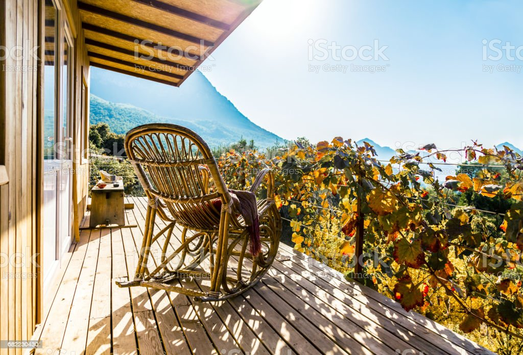 Rocking Chair on terrace of wooden cottage at warm sunlight stock photo