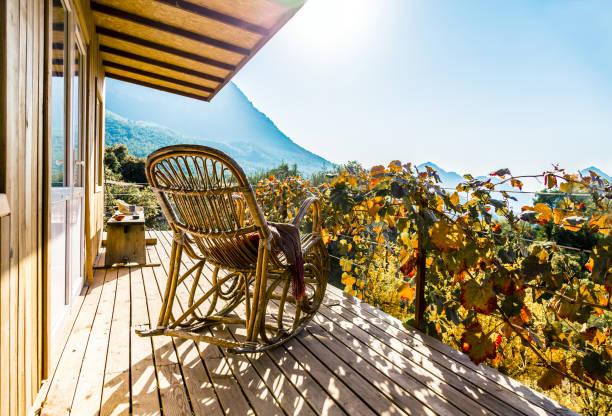 Schaukelstuhl auf der Terrasse des Holzhaus in warmes Sonnenlicht – Foto