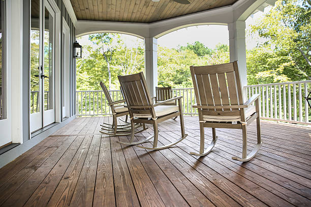 Rocking Chairs on a Southern Porch Rocking chairs grace a upper porch in a large lake front home in the Southern USA. southern usa stock pictures, royalty-free photos & images