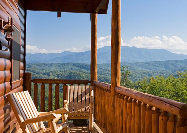 rocking chairs on the patio outside a mountain cabin - kütük ev stok fotoğraflar ve resimler