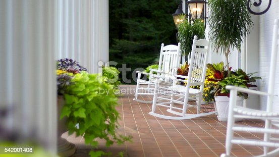 Rocking chairs sitting outside on the front porch of a home with white columns.
