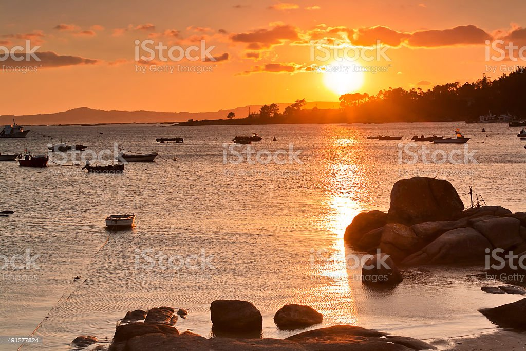 Rocks and boats at sunset stock photo