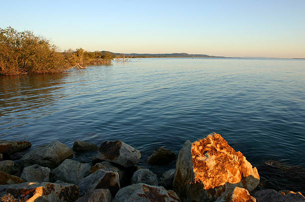 Rocks and Tranquil Bay Seascape at Sunset stock photo