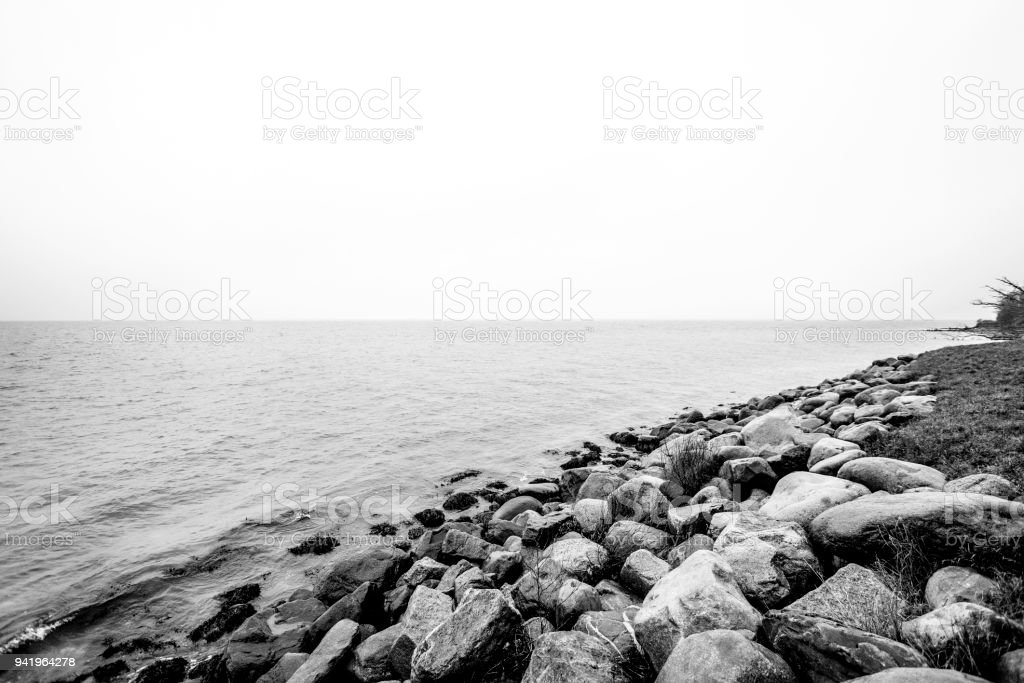 Rocks by the seashore in a black and white stock photo