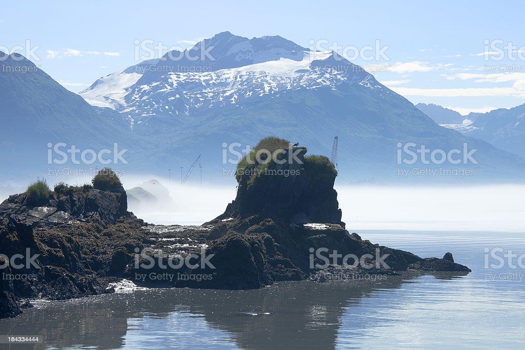 Rocks, fog, and Chugach Mountains in Valdez Alaska bay stock photo