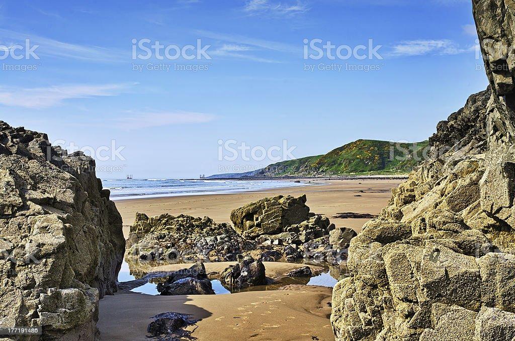 Rocks framing a view of Killantringan Bay stock photo