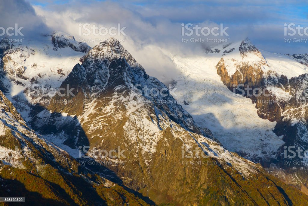 Rocks in Caucasus mountains by winter covered by snow with cloudy sky as a backckground. stock photo