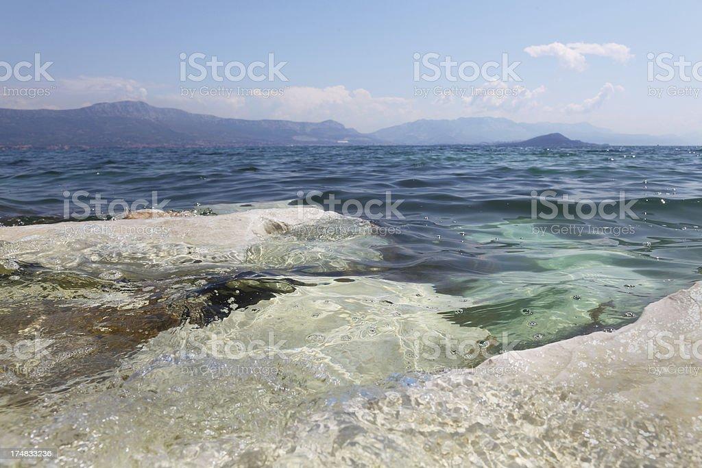 rocks in turquoise mediterranean pebble beach view Trogir Croatia royalty-free stock photo